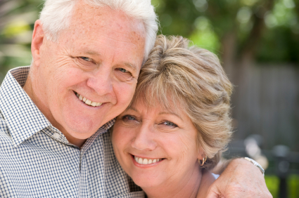 Senior couple smiling portrait outdoors. Soft focus background