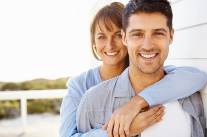 Portrait of attractive young woman embracing her husband from behind