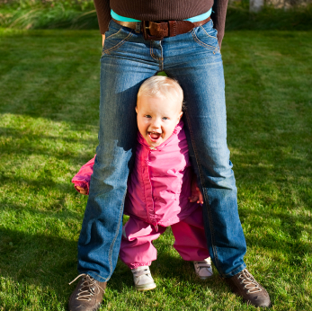 Cute little baby girl wearing pink suit standing with mother outdoors