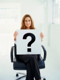 portrait-young-woman-sitting-chair-holding-sign-with-question-mark_1